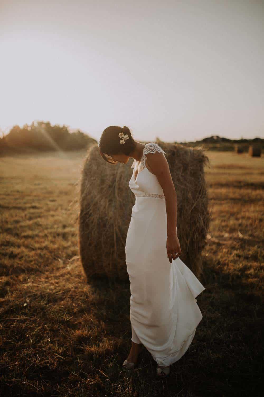 Une mariée dans un champs avec un photographe à Toulouse