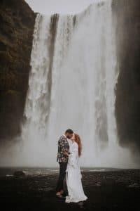 des mariés qui s'embrassent devant une cascade